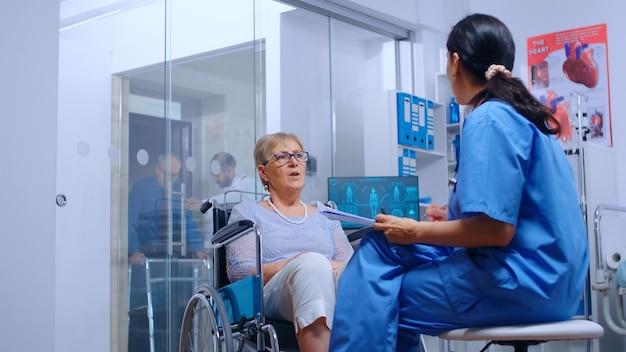 휠체어를 탄 장애인 노인 여성은 현대적인 회복 클리닉이나 병원에서 간호사와 이야기를 나눴습니다. 의사의 도움, 보행 장애가 있는 장애인 지원, 의료 및 치료