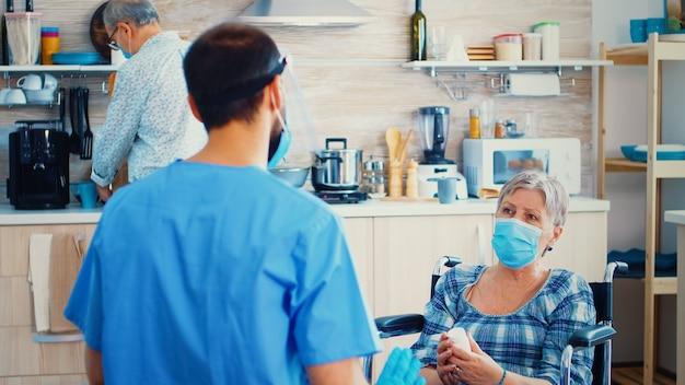 휠체어를 탄 장애인 노인 여성이 마스크를 쓰고 코로나바이러스 전염병 및 가정 방문 동안 치료에 대해 의사와 논의했습니다. 장애인 노인 여성에게 약을 제공하는 사회 복지사. 지