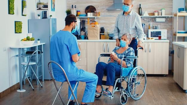 휠체어를 탄 장애인 노인 여성은 얼굴 마스크를 쓰고 치료에 대해 의사와 논의합니다. 장애인 노인 여성에게 약을 제공하는 사회 복지사. covid-19 확산 방지를 돕는 노인과 의사