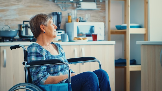 Handicapped senior woman in wheelchair standing alone in kitchen looking throug window. pensive thoughtful lonely woman in solitude. elderly disabled pensioner after injury and rehab, paralysis and di