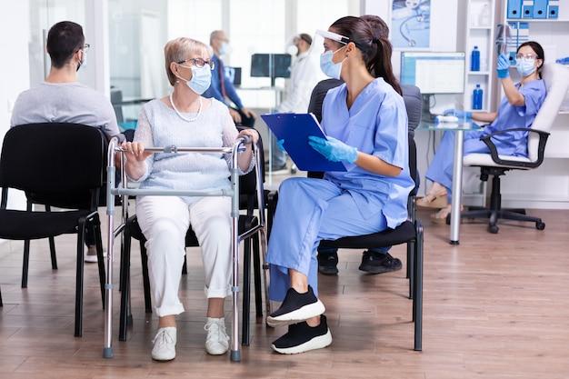 Donna anziana disabile con deambulatore nella sala d'attesa dell'ospedale utilizzando un deambulatore che parla con il personale medico del trattamento per la malattia durante la pandemia di coronavirus