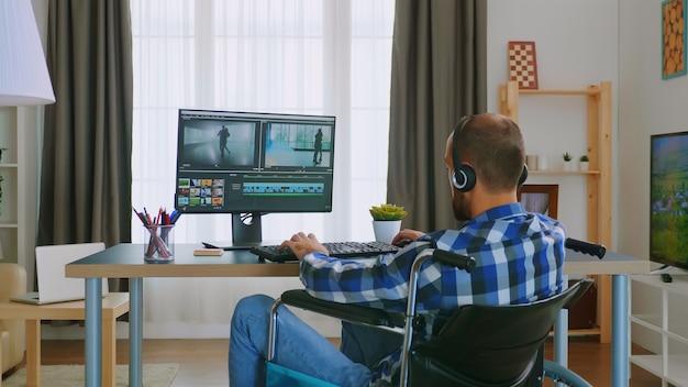 헤드폰을 끼고 집에서 일하는 휠체어 장애인 비디오 편집자.