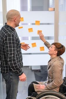 Женщина с ограниченными возможностями в офисе используя post-it отмечает