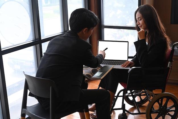 휠체어를 탄 장애인 여성이 동료와 함께 사무실에서 일하고 있습니다.