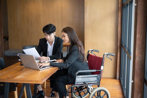 휠체어를 탄 장애인 여성이 사무실에서 동료와 함께 새로운 비즈니스 프로젝트를 진행하고 있습니다.