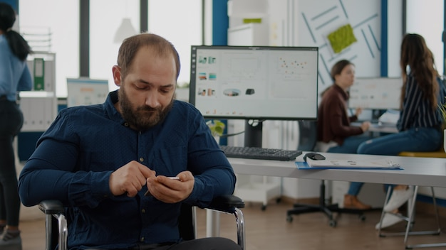 Handicapped young employee browsing on smartphone during worktime