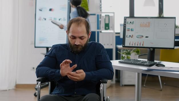 勤務時間中に携帯電話で検索する障害のある若い従業員