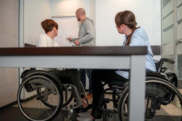 チームとオフィスで障害を持つ若い女性