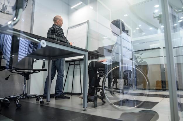 Giovane donna andicappata nella vista bassa dell'ufficio