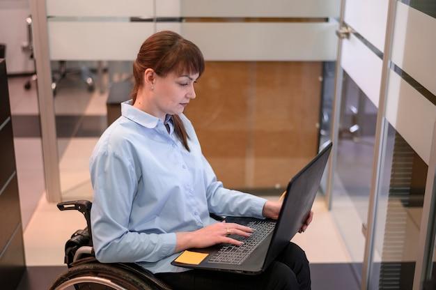 Giovane donna andicappata in ufficio che lavora al computer portatile