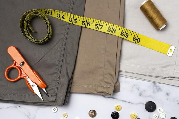 수공예품, 의류 수리. 위에서 화려한 배경을 가진 찢어진 청바지 바느질 액세서리. 플랫 레이