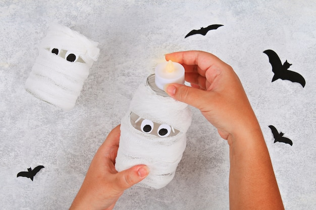 Handicraft from a jar. mummy from a jar and bandages and bats on a light table. diy.