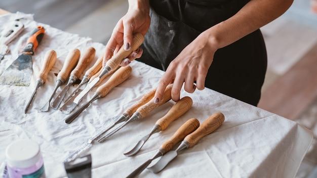テーブルの上に配置された手工芸品セット。彫刻およびモデリングツール。ノミで女性をクラフトします。選択。進行中のアートワーク。