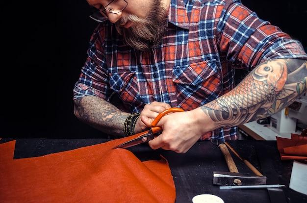 Ремесленник вырезает контуры кожи для своей новой продукции на рабочем месте.