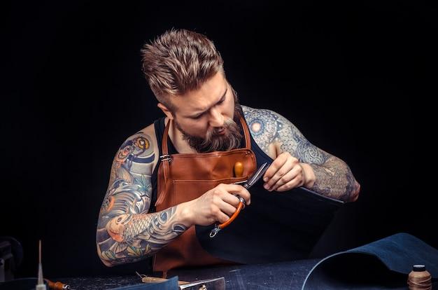Ремесленник, работающий с кожаными изделиями в студии