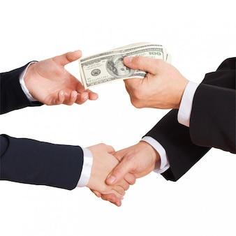 他の手と白い背景で隔離のハンドシェイクに現金ドルを渡します。