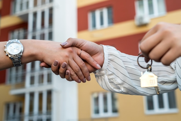 Handing the home keys between realtor and new owner. sale concept