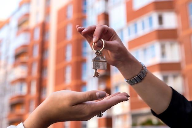부동산 중개인과 새 소유자 사이에 집 열쇠를 건네줍니다. 판매 개념