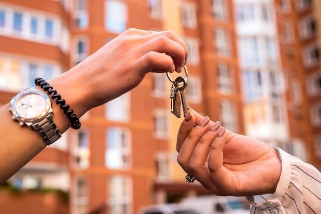 Передача ключей от дома между риэлтором и новым владельцем. концепция продажи