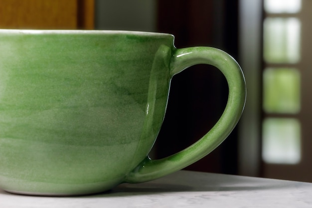 The handle of a modern green coffee mug