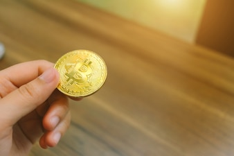 Handle of Bitcoin coin on wooden floor background.