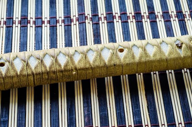 Рукоять японского меча катана на бамбуковой циновке