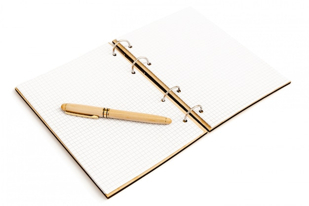 The handle in a wooden case with a cap lies on an empty sheet of an open notebook with a wooden cover.