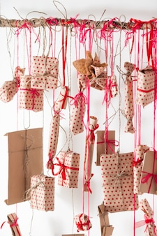 Handmade advent calendar hanging on a white wall. gifts wrapped in craft paper and tied with red threads and ribbons. wooden stick and many presents