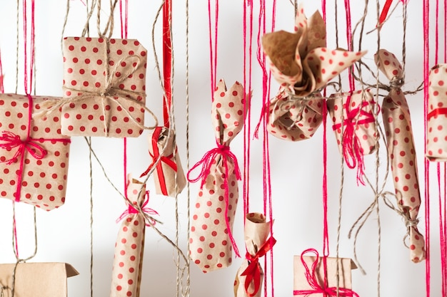 Handmade advent calendar hanging on a white wall. gifts wrapped in craft paper and tied with red threads and ribbons.