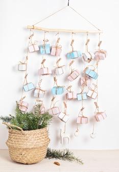 Рождественский календарь ручной работы с подарочными коробками на веревках и хвоей в плетеной корзине