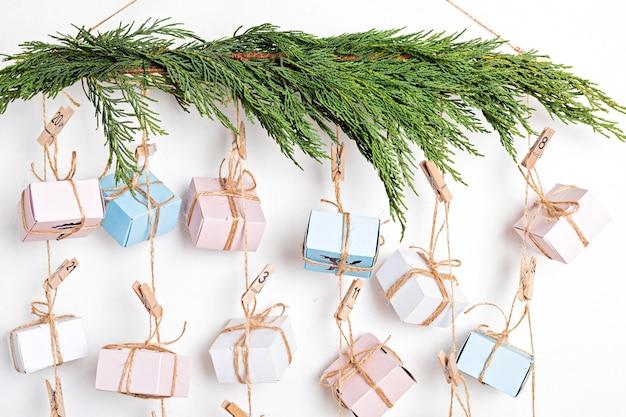 Адвент-календарь ручной работы с подарочными коробками на веревках