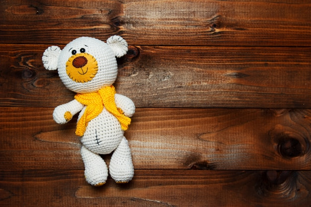 Handmade amigurumi teddy bear on wooden background.