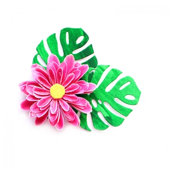 Handmade artificial paper flower brightly pink color and paper leaves of green monster in composition