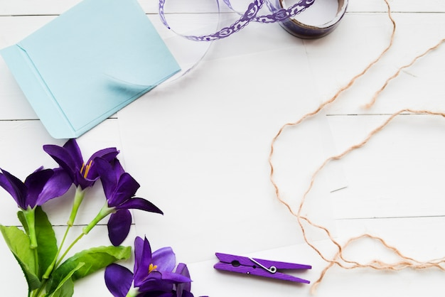 Handmade artificial purple flowers; paper; ribbon; clothespin and string on white plank backdrop