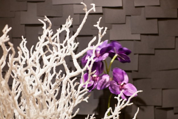 手作りの人工白雪の枝、暗い背景に紫色の花