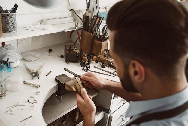 수공. 그의 작업대에서 반지를 만드는 젊은 남성 보석상의 뒷모습. 주얼리 제작 과정. 보석 장비. 작업 과정. 보석 제조 개념입니다.