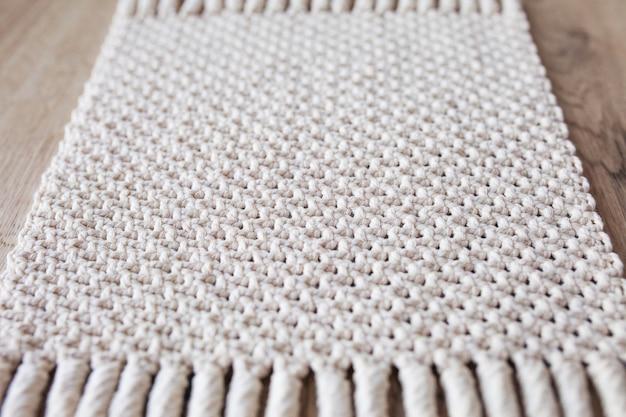 手作りベージュマクラメ背景。マクラメのテクスチャ、環境に優しい、モダンな編み物。木製のテーブルにマクラメ絨毯