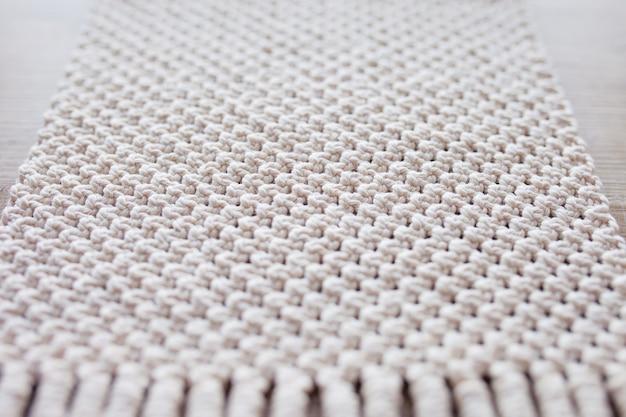 Handmade beige macrame background. macrame texture, eco friendly, modern knitting. macrame rug on wooden table