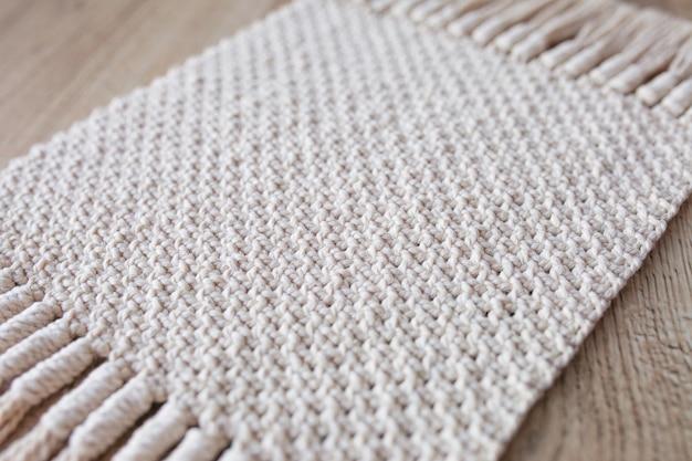 手作りベージュマクラメ。マクラメの質感、環境にやさしい、モダンな編み物。木製のテーブルにマクラメの敷物