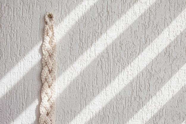 手作りのベージュのマクラメ柄。マクラメの質感、環境にやさしい、モダンな編み物。白いテクスチャの壁にマクラメの結び目。コピースペース