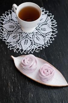 Ручной ягодный зефир, чашка чая и белые салфетки на черном фоне старинных деревянных.