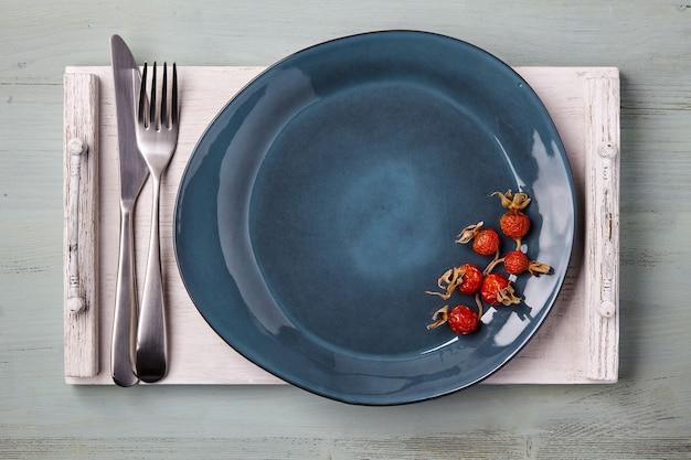 Голубая керамическая тарелка ручной работы, украшенная сушеными плодами шиповника, со столовыми приборами на белом деревянном подносе. меню. вид сверху