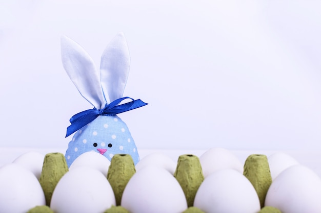 Handmade blue hare looks out from behind a tray of eggs,  happy easter  greeting card .