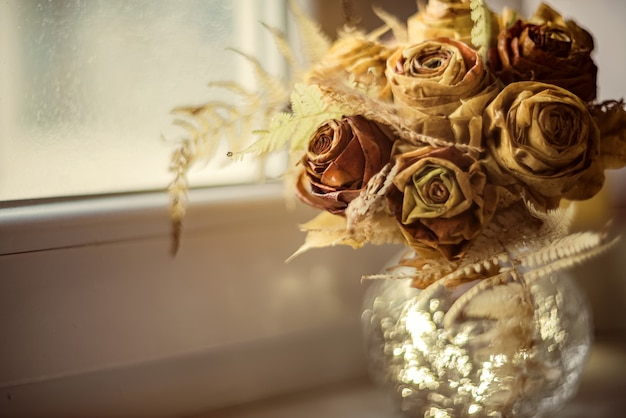Handmade bouquet of autumn roses made from maple leaves stands in round vase on the windowsill. home interior and decorating