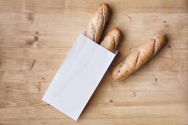 Хлеб ручной работы в бумажном пакете на столе
