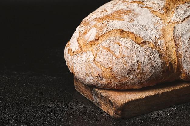 Handmade bread on a wood cutting board on black