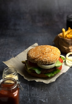 Handmade burger with fries and coke with straws