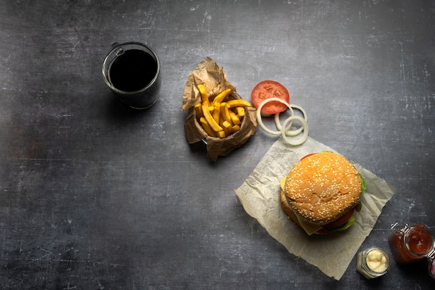 Handmade burger with fries and onion rings and coke