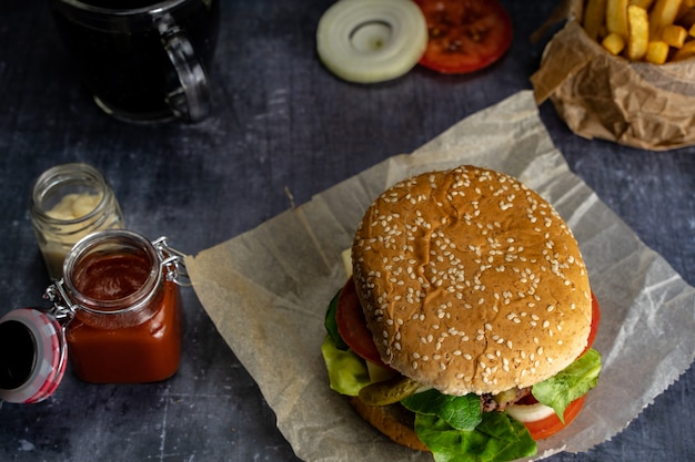 Handmade burger with fries with ketchup and red cloth