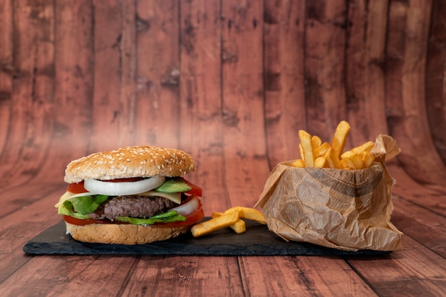 Handmade burger with fries on wooden table